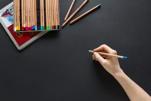Freelance designer drawing with colored pencils. Designs can be sold for passive income