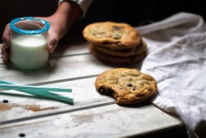Chocolate chip cookies on wood table with milk and blue straws