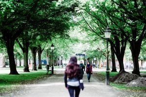 Woman walking outside with trees surrounding her for daily motivation