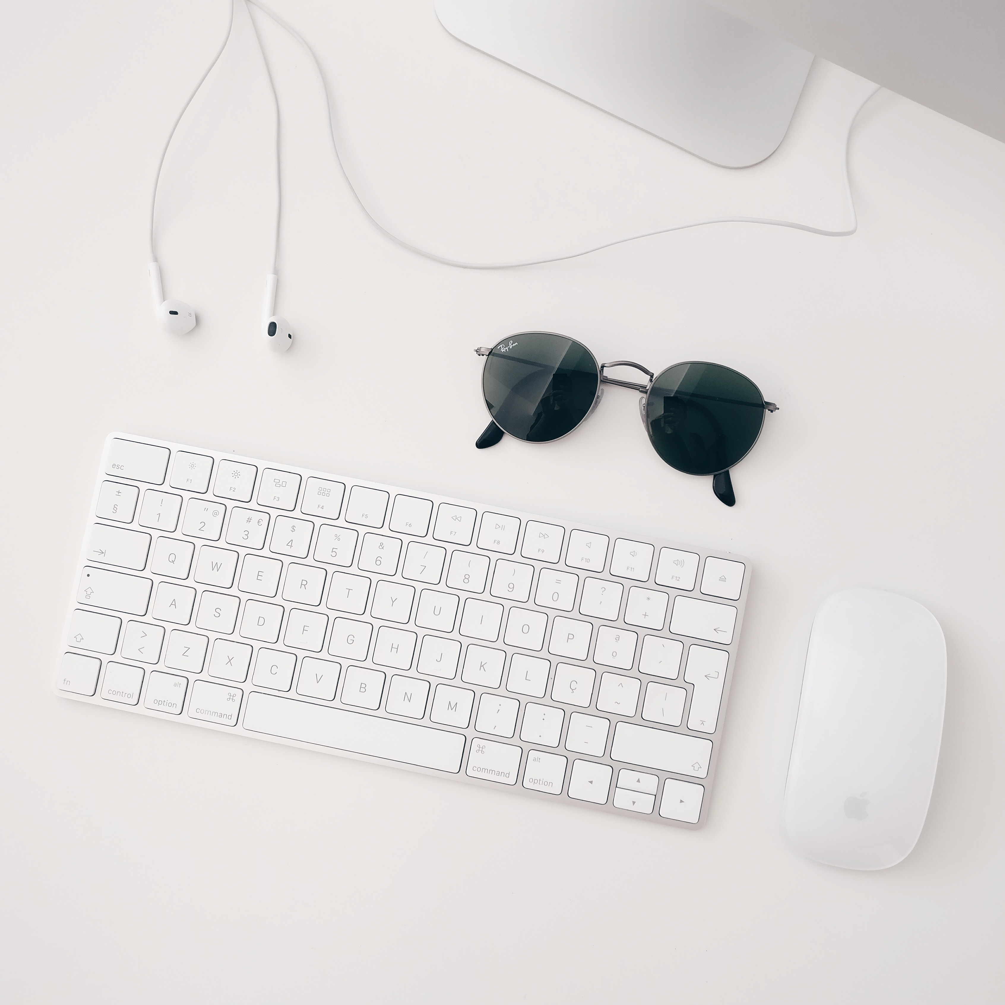 white computer and dark sunglasses on white desk