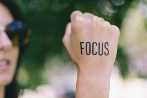 The word focus written on a woman's fist.