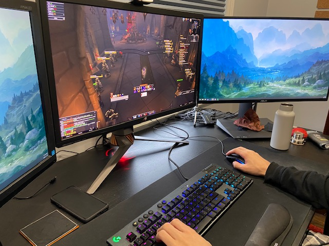 Image of freelance game developer with 3 computer screens working at development